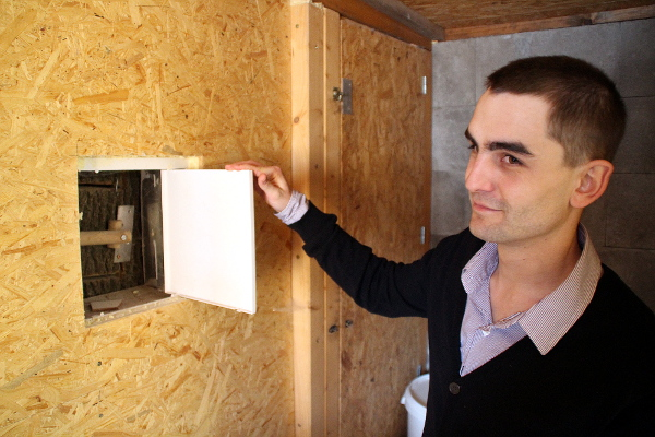 Ondřej Štafek ukazuje jeden z kontrolních otvorů do boudy arů vojenských, který vede skrz zeď do vedlejší místnosti (Foto: Jan Potůček, Ararauna.cz)