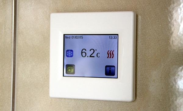 Termostat s dotykovým displejem, který je nastavený na 7°C. Červené proužky vpravo znamenají, že panely topí. (Foto: Jan Potůček, Ararauna.cz)